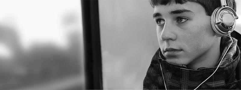Boy wearing headphones staring out of a window